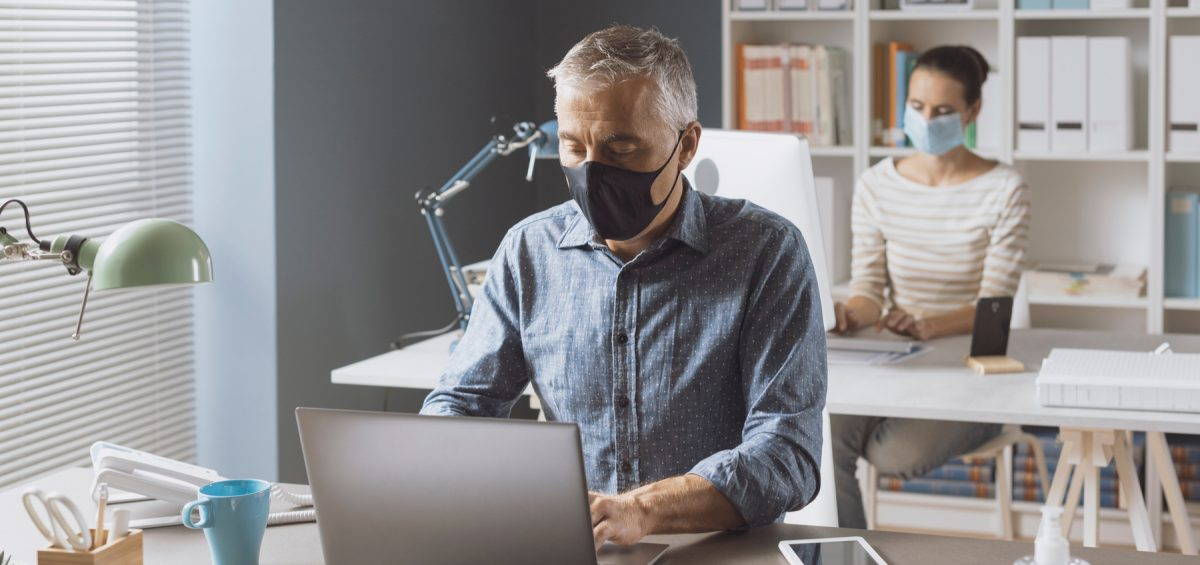 man with a mask typing on a computer